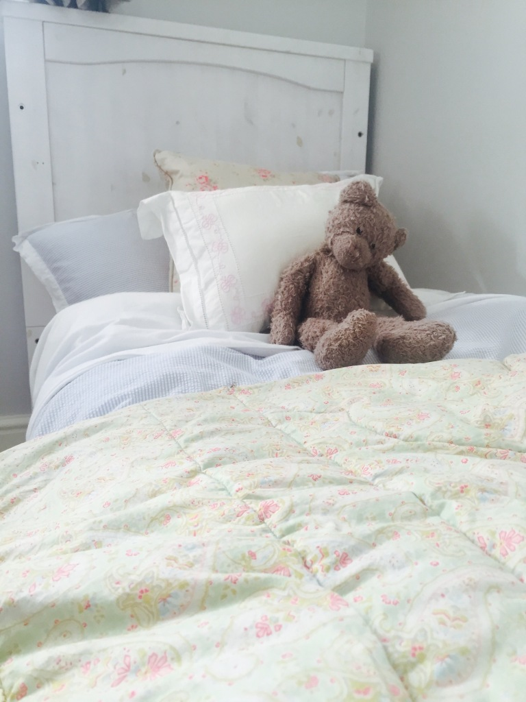 old teddy bear on childs bed
